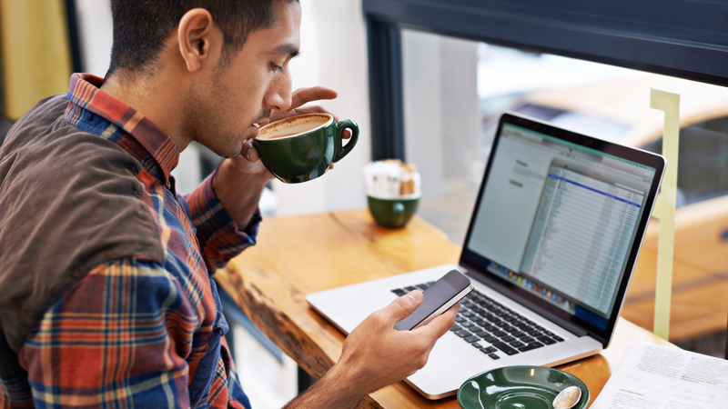 Seated man sipping coffee in front of window with a laptop, using a smart phone.