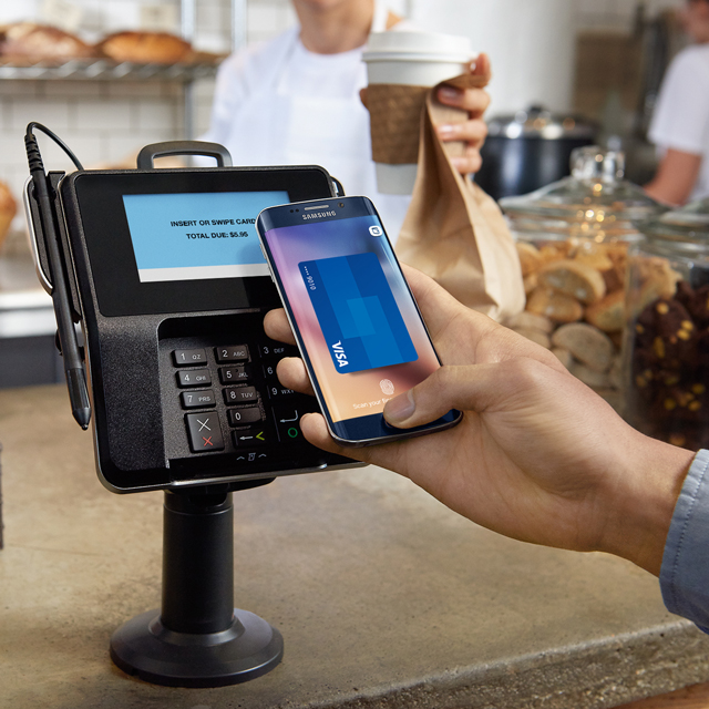 Using Samsung Pay on mobile device at coffee shop.
