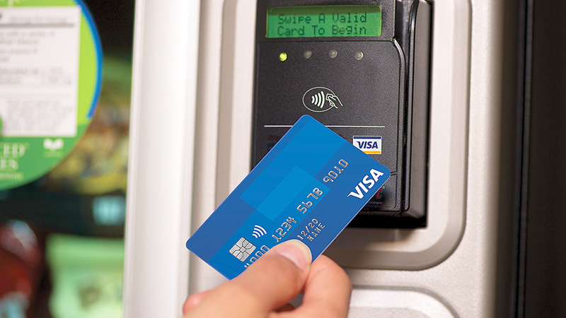 Person tapping contactless Visa card on contactless enabled payment terminal.