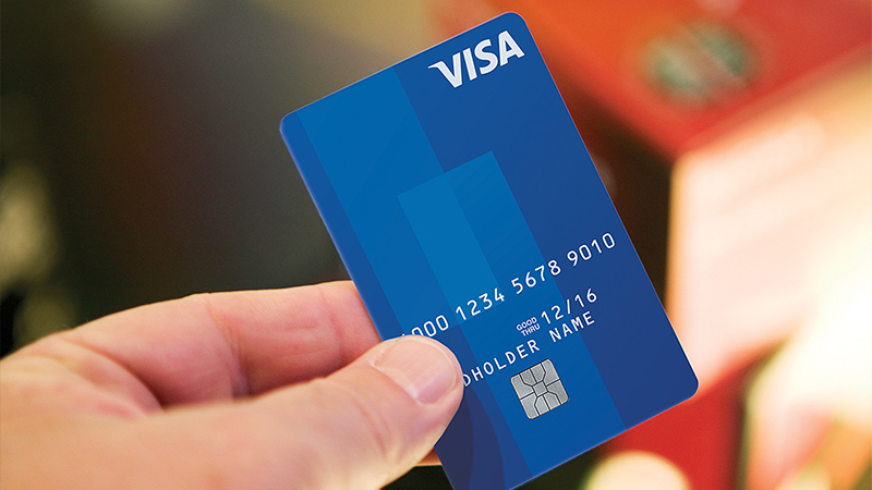 Person holding Visa chip card.
