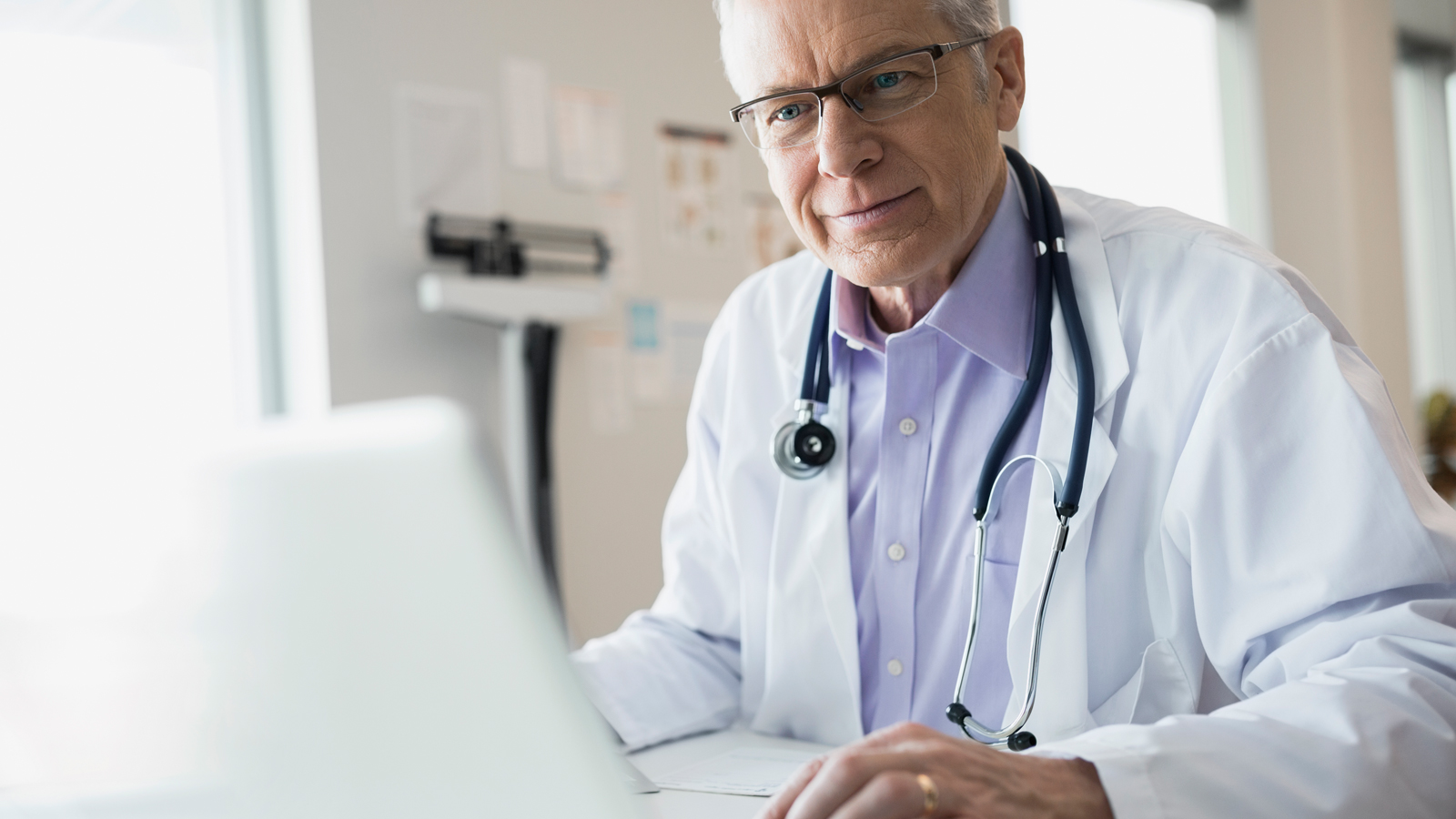 Doctor in office using laptop.