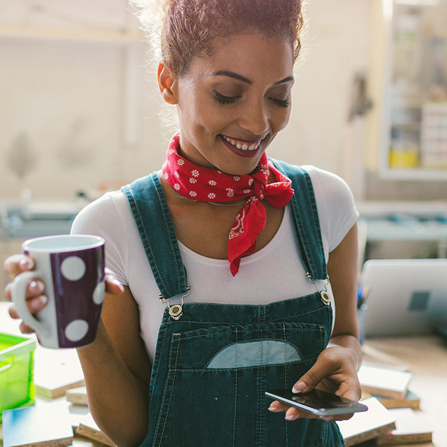 Young woman holding a cup of coffee while looking at her smartphone in her workshop